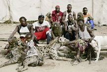 """Pieter Hugo. The Hyena Men of Abuja, Nigeria 2005 / South African photographer. """"Myths surrounded them. ... A group of men, a little girl, three hyenas, four monkeys and a few rock pythons. It turned out that they were a group of itinerant minstrels, performers who used the animals to entertain crowds and sell traditional medicines. The animal handlers were all related to each other and were practising a tradition passed down from generation to generation."""" http://www.pieterhugo.com/the-hyena-other-men/"""