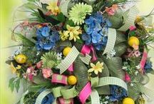 """Deco Mesh Springtime Wreath / This is about How to Make a Springtime Deco Mesh Wreath. I show you in step-by-step, detailed instructions how YOU can make a beautiful deco mesh wreath just like this one. I started with green Deco Mesh, and added four different types of ribbon for bows and loops spread throughout Then I show you how to add many different types of greens, flowers, and – yes – lemons. This wreath had a """"WOW FACTOR"""" of over a 10!!! / by Ladybug Wreaths"""