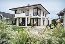 München-Poing - Stadtvilla / Ein echter Hingucker ist dieser Entwurf von WeberHaus. Erker, geschützte Terrassen und Balkone verbinden sich auf der südlichen Giebelseite zu einem symmetrischen System.   Konzipiert wurde das Haus als Mehrgenerationenhaus, es können bequem zwei Familien in ihm leben. Das Erdgeschoss bietet mit etwa 127 qm Wohnfläche ein schönes zu Hause beispielsweise für die junge Familie, während die Eltern sich im Dachgeschoss auf etwa 99 qm einrichten können.