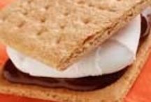 "Smores / The first recorded version of the S'more recipe can be found in the Girl Scout handbook ""Tramping and Trailing with the Girl Scouts"" of 1927. Wondering how to make a S'more, sandwich a toasted marshmallow and a piece of chocolate between two graham crackers."