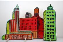 "POp uP CiTy / I painted 66 individual buildings on 1/4 "" birch plywood. These are cut out and stand up on slotted tabs.  Much like the paper dolls i made as a kid.  These will be installed at Gallery 360 in Minneapolis, MN for my solo show, "" Pop Up City"".  Opens Nov 10, 2012."