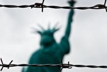 """Liberté, liberté chérie / Il s'agit d'une expression tirée du sixième couplet de La Marseillaise, l'hymne national français.   La Statue de la Liberté représente une femme drapée dans une toge, brandissant une torche de la main droite. Les sept rayons de la couronne représentent les sept mers et continents. Sur les tablettes qu'elle tient de la main gauche sont inscrits, en chiffres romains, """" 4 juillet 1776 """". A ses pieds se trouvent les chaînes brisées de l'esclavage."""