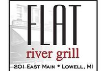 Flat River Grill / Flat River Grill is a treasure, providing Lowell with a wonderful location for quality dining, refreshing ambiance and community camaraderie. Transformed from the historic Bergin building on main street and nestled alongside the Flat River and Lowell Showboat, Flat River Grill offers its guests a nostalgic atmosphere and warmth.
