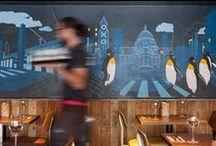 Zizzi Bankside / Just a short walk from the famous Globe Theatre, our Bankside restaurant offers a nice rest for the weary London sightseers and stunning river views while you dine. The illustrations decorating the restaurant were created for us by Emma-Louise Jones and are inspired by the surrounding areas architecture and hustle and bustle of the city. Matthew Brooks has designed some skateboard decks for us based on the hub of urban skateboard culture that involves spirit, music and fashion.