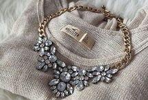 Naszyjniki / Wśród modnych naszyjników dominują dwie tendencje: duże, wyraziste kolie z mieniącymi się kamieniami oraz delikatne łańcuszki z małymi zawieszkami, które stały się ulubioną biżuterią gwiazd. Masywne naszyjniki z kwiatowymi motywami lub w formie złotych łańcuchów są nie tylko dopełnieniem wieczorowych kreacji, ale także noszone są w codziennych stylizacjach do sukienek lub t-shirtów.