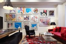 Wall Street Apartments | Axis Mundi Design / Good design must reflect the personality of the client. So when siblings purchased studios in Downtown by Philippe Starck, one of the first buildings to herald the revitalization of Manhattan's Financial District, the aim was to create environments that were truly bespoke. The brother's tastes jibed synchronously with the insouciant idea of France's most popular prankster converting a building that once housed the buttoned-up offices of JP Morgan Chase. His collection of Takashi Murakami works, the gallery-like centerpiece of the main area, announces his boldness and flair up front, as do furnishings by Droog, Moooi and, of course Starck, as well as hide rugs and upholstery, and a predominantly red palette. His sister was after something soothing and discreet. So Axis Mundi responded with a neutrals and used glass to carve out a bedroom surrounded by drapes that transform it into a golden cocoon. Hide (albeit less flamboyantly applied) evokes a familial commonality, and built-in furniture and cabinetry optimize space restrictions inherent in studio apartments.   Design Team: John Beckmann, with Richard Rosenbloom Photography: Mikiko Kikuyama © Axis Mundi Design LLC