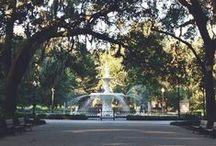 Forsyth Park Fountain / The Fountain is a large, ornate, two-tiered cast-iron fountain surmounted by a classically robed female figure standing in extreme contrapposto, holding a rod. Water comes from this rod into the top basin. The top basin appears to be made of three successive rows of closely arranged flat leaves, around the base of which are arranged acanthus leaves. The pedestal which supports this top basin is surrounded by grasses, including cattails, and a wading bird with wings outspread.