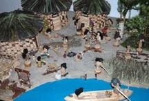 Il villaggio neolitico / Laboratori didattici di archeologia imitativa. Ricostruzione di un villaggio Neolitico con vari personaggi legati alle attività dell'epoca.