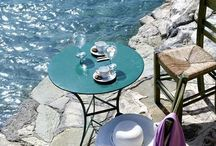 By The Sea / A table by the sea. Breathe in the salt air and soak up the sun or moon. Dining by the sea.