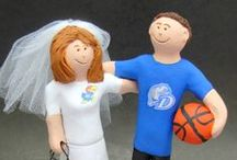 "Basketball Wedding Cake Toppers /  ""Slam Dunk!!"" for true love with these custom made wedding cake toppers by www.magicmud.com 1 800 231 9814,  handmade for basketball fans and players alike! If you want to be in team jerseys or gown and suit...or a combination of those...with a basketball, pennant, beer or foam finger!!  whatever you want is what you get as we make these kiln fired figurines by hand for you....and have been doing so for over 35 years!"