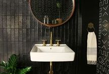 Tribal Black Bathroom / When Amber Lewis of Amber Interiors started designing her first brick-and-mortar shop and studio in downtown Calabasas, CA, she knew she wanted something extra-special for the bathroom. Lewis opted for deep black paint over tile walls, bold tribal-pattern wallpaper of her own design, and a simple wall-hung sink paired with a gleaming gold faucet. The result is a space that perfectly reflects her style and inspires those lucky enough to visit this jewel-box of a space. / by Kohler Co.