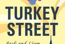 Turkey Street / Six months into their Turkish affair, Jack and Liam, a gay couple from London, took lodgings in the oldest ward of Bodrum Town. If they wanted to shy away from the curtain-twitchers, they couldn't have chosen a worse position. Their terrace overlooked Turkey Street like the balcony of Buckingham Palace and the middle-aged infidels stuck out like a couple of drunks at a temperance meeting.
