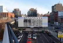 High Line Billboard / Since 2010, the High Line Billboard series has presented works of art on a billboard space adjacent to the High Line at West 18th Street and 10th Avenue. Each work in the series is installed for one month, alternating with an advertisement by ParkFast.com, the owners of the billboard. Featured artists have included John Baldessari, Paola Pivi, Allen Ruppersberg, Gilbert & George, and Thomas Demand, among others.