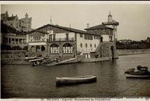 Arriluze / El paseo hasta el viejo puerto y las galerías de Punta Begoña, los chalets de Atxekolandeta, la Cruz Roja del Mar, antes Estación de Salvamento de Náufragos, Y la grúa Titán, utilizada durante la construcción del contramuelle (1896-1903), que se conservó en el arranque del dique hasta 1972 / by Getxo iruditan - Imágenes de Getxo