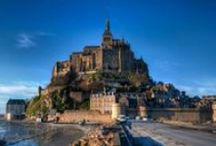 """Mont Saint-Michel / """"Wonder of the West"""", the Mont-Saint-Michel stands at the heart of an immense bay invaded by the highest tides in Europe. It was at the request of Michael the Archangel, """"head of the heavenly armies"""" that Saint Aubert, bishop of Avranches, built in 708 and consacrated this first church on 16th October 709. In 966, at the request of the Duke of Normandy, a community of Benedictines established themselves on the rock."""