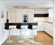 Küchen nach Maß in Borken / Weiße Küche grifflos mit Granitarbeitsplatte, Glasschiebetüranlage als Raumtrenner individuell nach Maß von www.klocke.de