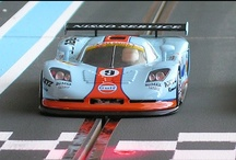 Slot Car Racing / Slot racing is racing with model cars on a plastic or wooden track. An electrical engine powers the cars. The motor is connected to a guide that is positioned under the chassis of the model. To the guide are copper braids connected and is positioned in a slot in the middle of parallel rails. The slot car gets speed if the driver gives power to the rails by means of a hand held controller.