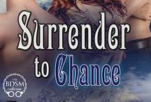 Surrender To Chance - KB3 / Book Three in the King's Bluff, Wyoming series. Olivia Fletcher, returns to King's Bluff to look after her divorce. Alex and Kane MacKenzie, billionaire tycoons and former  SEALs, have opened up their private guest lodge and BDSM Club located on secluded land outside of the town. They need a PR consultant, one who is a local and has the trust of the town. Olivia needs a job. Sparks fly!