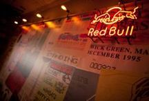 Revolution Bar: Red Bull Bar / As a large supplier to Vodka Revolution, Red Bull were given the opportunity to brand a large part of their new bar in Blackpool, UK.  Pop Store worked with closely with Red Bull and Revolution to implement Red Bull themed areas around the new bar. Old music posters were reproduced and created the feature backdrop to the stage area – with a Red Bull neon to the centre of the stage.
