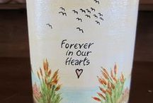 Scattering Urns / Scattering or green burial sharing urns have an easy-to-open top for casting the ashes of your loved one or beloved pet out into water or nature. These urns are completely biodegradable and safe for the environment. They can be used as burial urns for memorable green burials. All of our scattering or green burial urns feature handmade and freehand painted wrap-around designs that make them truly one of a kind.