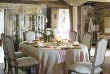 French country style / francia vidéki stílus / Characteristics: stone or plaster walls, natural stone, clay or brick flooring, warm and casual, contrasting texture and color, shades of yellow, gold, red, bright grass green, dark green, ocean blue, black and grey, levander, rusted metal furniture, use of natural materials, beamed ceilings, carved wood, woven chairs, wool and cotton rugs, stone fireplace, provencal print fabrics, armoir, large dining table, toile, tablecloth and curtains with levanders, olives, roosters, sunflowers.