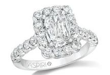 Aspiri / Our engagement ring collection appeals to the bride looking for a classic style with a modern sensibility. All rings are complete and feature a dazzling ASPIRI™ cut center stone, one that looks 25% – 50% larger than a similar stone of equal carat weight, faceted for maximum brightness and sparkle. A fine-quality halo setting enhances its sophistication and accentuates the center diamond, resulting in a gorgeous ring that is both impressive and affordable.
