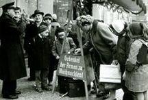 """""""Topfstehen"""" – die Red Kettles / Traditionell sammelt die Heilsarmee in der Vorweihnachtszeit in Fußgängerzonen auf der ganzen Welt Spenden, welche u.a. für Weihnachtsfeiern für Bedürftige verwendet werden. Dazu verwendet sie meist die so genannten """"Red Kettles"""" (roten Töpfe), die auf einem dreibeinigen Stativ montiert sind."""