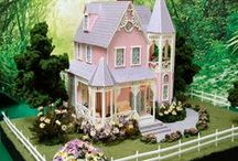 """Miniature Dollhouse in Quarter Scale Victoria Rose / Victoria Rose - Handcrafted Miniature in quarter scale at Norman's Country Creek. Dollhouse is 8.5""""L x 10.25""""H x 7.5""""D.  It sits on a board that is 17.5"""" x 12.5""""."""