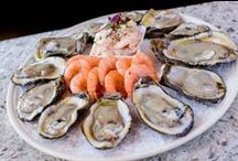 We DESIRE Seafood. / Take your seat in our cozy historic streetside bistro overlooking Bourbon Street. Often referred to as the most photographed corner in the French Quarter, the entrance to Desire boasts iconic Broadway style lights over its doorway. Relax at the historic oyster bar and be entertained by our oyster shuckers as they open and serve fresh salty Louisiana oysters.