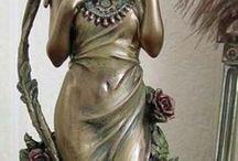 """,, ART NOVEAU - SECESE ,, / """"Krásná epocha"""" – přelom století Na rozdíl od velmi zdobených šatů z minulého období, byla pro módu """"krásné epochy"""" typická větší jednoduchost. Štíhlost ženského pasu kontrastovala se širokými rameny a hladkou zvonovitou sukní. Dojem křehkosti zvyšovaly i vyčesané účesy a drobné okrouhlé kloboučky - kapotky. Šaty byly stále dvojdílné, kabátek byl však redukován jen na živůtek.  Rukávy, tentokrát všívané vysoko s drobnými záhyby.Klobouky, rukavice a kabelky byly pro dámu stále nezbytností."""