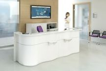 WAVE reception desk / Shaped with simple elegance, our new Wave reception impresses with a subtle ocean wave design expressing a sense of calmness. The white Lacobel glass top with the added decorative strips at the front and bottom, add to its fresh and sleek appeal.  The Wave gracefully adapts to one's individual needs and tastes. For this reason, it is available in a variety of modules and colors. Standard front comes in white, blue, orange and green.