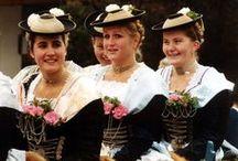 Central DE S: BY Miesbach / Kenmerkend voor de Miesbacher Tracht zijn de dirndljurk met lange mouw, de rok in dezelfde kleur, een witte blouse en wit schort, witte zijden kousen en zwarte leren klederdrachtschoenen. De traditionele kleuren voor de rok en het lijfje zijn blauw of wijnrood.