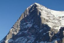 """Eiger / The North face of the Eiger is one of the great north faces of the Alps. The Eiger is a 3,970-metre (13,020ft) mountain of the Bernese Alps, overlooking Grindelwald and Lauterbrunnen in the Bernese Oberland of Switzerland, just north of the main watershed and border with Valais. It is the easternmost peak of a ridge crest that extends across the Mönch to the Jungfrau at 4,158m (13,642ft), constituting one of the most emblematic sights of the Swiss Alps. With a length of up to four kilometres  the ascent routes through the north face belong to the longest and most exhausting ones in the Alps; risk of rockfalls and avalanches is high. The Eiger has been highly publicized for the many tragedies involving climbing expeditions. Since 1935, at least sixty-four climbers have died attempting the north face, earning it the German nickname Mordwand, literally """"murder(ous) wall""""—a pun on its correct title of Nordwand (North Wall)."""