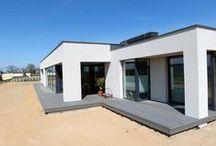Taras kompozytowy w Rogalinku / Taras kompozytowy Twinson wykonany na płycie betonowej z podkonstrukcją drewnianą z drewna bangkirai. Pomimo, że w płaszczyźnie tarasu była wykonana płyta betonowa, za obopólnym porozumieniem z inwestorem wykonaliśmy podbudowę krzyżową, celem zwiększenia nośności tarasu i stabilności płaszczyzny. Ponadto, podkonstrukcja przewidywała zamontowanie blach ze stali nierdzewnej umożliwiającym montaż desek nad metalowymi parapetami, tak, aby ich nie uszkodzić podczas eksploatacji.