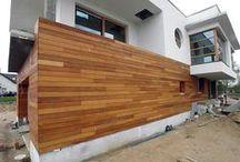 Elewacja drewniana z Garappy. Realizacja w Cigacicach. / Elewacja budynku mieszkalnego jednorodzinnego wykonana z drewna Garapa z przerobionej w naszej stolarni deski tarasowej. Profil elewacyjny jest gładki i przezierny, co daje systematyczne wietrzenie połaci elewacji. Na ściany z cegły zamontowano legarowe elementy podkonstrukcji. Podkonstrukcja do ściany jest zamontowana punktowo, tak, aby nie tworzyć mostków termicznych. Wszystkie legary są wykonane z drewna bankirai, odpornego na wilgoć i korozje biologiczną.
