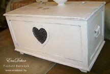 Szives provence asztal lada / A provence-i stílus jegyében készült antikolt fehér tömörfenyő kincsesláda fém veretekkel. Két oldalán kivágott szív forma, fém hálóval befedve. Ágynemű, takarók, anyagok, terítők, újságok, egyéb kincsek tárolásához remek választás. Kanapé melletti asztalnak is ideális. Vidéki hangulat a nappaliban, hálószobában, előszobában, gyerekszobában. Megrendelhető az EraDekor-nál. További információ: www.eradekor.hu