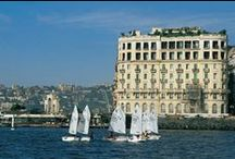 Hotel Excelsior - Naples / Located by the magnificent Bay of Naples and welcoming guests since December 1908, the Hotel Excelsior is a historic landmark steeped in tradition, and occupies a prestigious place on the seafront. It offers spectacular views of Mount Vesuvius, the island of Capri and the Sorrento coastline. Hotel Excelsior combines the breathtaking views and the elegant beauty of Naples with modern luxury and a touch of antiquity.