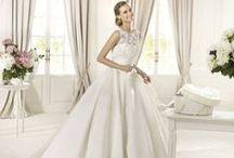 Dalia - Pronovias / Klasszikusan elegáns, deréktől bővülő, nagy szoknyás szatén esküvői ruha, melynek zárt, csipkés felsőrészét gyöngyök és flitterek díszítik. A magasítottan szabott derékrész tökéletesen kihangsúlyozza a karcsú derékvonalat és a zárt felső vállrésze biztonságot nyújt viselőjének!