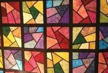 Stained Glass Quilts / Quilts that give the impression of stained glass. Typically bright colored motifs or blocks separated by thin dark strips in some way.