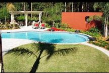 Red Wall Design / This custom designed and built space by 5 Star Outdoor Design is one of the most memorable. When walking into the backyard of this Jacksonville, FL home the first thing you notice is the striking red wall that looks amazing next to the gorgeously shaped pool. The fire pit, pergola and water bowl features next to the pool help make this backyard perfect for anything. Also, the outdoor kitchen and bar area help make this space even more versatile.
