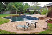 Backyard Patio Design / This outdoor pool and patio custom built by 5 Star Outdoor Design is uniquely constructed. The patio of this Jacksonville, FL home was partial built up to create a nice seating area and a beach rock and stepping stone area that looks out over the pool. The waterfall coming off the wall of the upper patio and falling into the pool tie the upper and lower patio areas together great.
