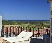 """Sardinien: Li Conchi - Cala Sinzias / Im Schutze der immergrünen Hügel des Naturreservats des Parco dei Sette Fratelli liegt diese außergewöhnliche Ferienhausanlage im Südosten Sardiniens, nur 2 km vom Traumstrand """"Cala Sinzias"""" entfernt. Die faszinierende Architektur der Anlage erschafft eine einzigartige Sinfonie aus Meer, Natur und Granit, den uralten Elementen Sardiniens. Das Herzstück von Li Conchi bildet ein großer Gemeinschaftspool mit abgeteiltem Kinderbereich."""