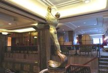 Goddess of Dawn at Hotel Phillips / A TRADITION OF CLASS AND LUXURY: At Hotel Phillips, the elaborate bronze and nickel metalwork, lustrous walnut paneling, Art Deco historic design and style have graced the lobby since 1931.  Back then, as now, gazing over the lobby is a gilded 11-foot likeness of the goddess of Dawn, known as the mother of the stars. Plenty of stars have certainly glided past the gleaming marble walls over the decades as well as hotel guests tradition to kiss the Goddess for good luck in love and fortune.