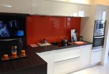 Studio style kitchen by Tierney kitchens. / Here's a nice neat little white gloss kitchen recently installed by us,with orange glass back splash and floating wall shelves,ideal for a small kitchen area but has everything you need at your fingertips,even a plasma TV!!!