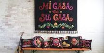 Fiesta Collection / This dramatic collection, inspired by the colours and symbols of Latin America, is made from black felt wool and appliquéd with bright and bold motifs. The main message 'Mi Casa es Su Casa', meaning 'My Home is Your Home', is embroidered upon wall hangings and cushions. The heart motif and the words 'Love' and 'Amor', which are intrinsic to Jan's work, also make a stand, embroidered upon cushions and throws.