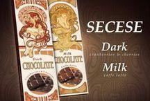 Kolekce v secesním stylu / Unikátní kolekce čokolád v designem v secesním stylu. Hořká a mléčná čokoládu s nevšedními příchutěmi a v neobvykle velkém balení 30 x 9 cm. Vybírat můžete z mléčné čokolády s příchutí caffe latte, sušenkami a kávou nebo hořké čokolády s kousky brusinek a višní.