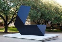 """Tony Smith / Tony Smith's first sculptures were small geometric forms using the cube, rhomboid, and tetrahedron as basic """"building blocks,"""" which he arranged as modules in a linear configuration. He developed this method, using large sheets of plywood. Smith passed these prototypes to industrial fabricators to produce the final version in sheet metal painted black. """"Amaryllis""""is located the Fine Arts Complex on Trinity St. at the University of Texas at Austin. GPS: 30.286942,-97.731779"""