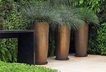 Eco Luxe - 2015 tuintrend / De tuin als oase van rust in een natuurlijke omgeving maar wel met behoud van strakke lijnen. Kenmerken zijn eenvoud, natuurlijke luxe, overzicht en ruimtelijkheid. We zien ruwe en industriële materialen naast elkaar, ruwe stenen naast glad rvs. De meest gebruikte materialen zijn: hout, natuursteen, beton, metaal en luxe keramiek. Metallic- en goudtinten worden als extra luxe gebruikt naast de grijs/groentinten, okergeel, zwart en wit. Beplanting wordt gekozen om de bijzondere bladuitstraling.
