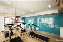 Fitness / Sala fitness na poddaszu. Nowoczesne wnętrze wykończone w drewnie, betonie szalunkowym i szkle.