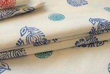 """Indien light / Hur mycket jag än älskar Indiens färgsprakande mönster kan jag ibland uppleva det som överväldigande i mitt stilrena svenska hem där """" less is more"""" principen gäller. Därför skapar jag också egen design där jag själv trycker materialet. Jag skapar en Indien Light version.Träblocken jag använder är gjorda för hand av skickliga hantverkare i Indien. Jag hoppas INDIRA kommer att ge Dig mycket inspiration och glädje."""